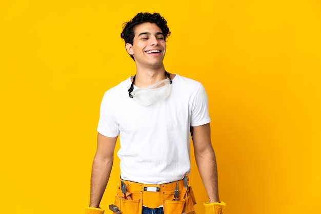 Venezolaanse elektricien man geïsoleerd op gele achtergrond lachen