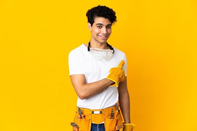 Venezolaanse elektricien man op geel wijst naar de zijkant om een product te presenteren