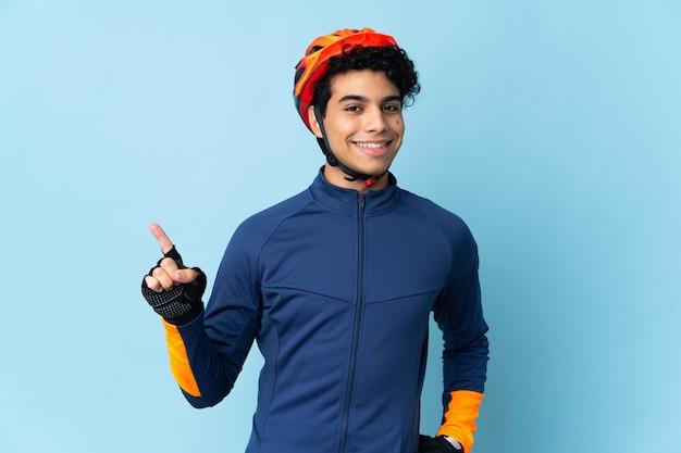 Venezolaanse fietsermens die op blauwe achtergrond wordt geïsoleerd die en een vinger opheft als teken van het beste