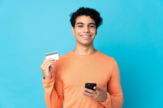 Venezolaanse man geïsoleerd op blauwe achtergrond kopen met de mobiel met een creditcard