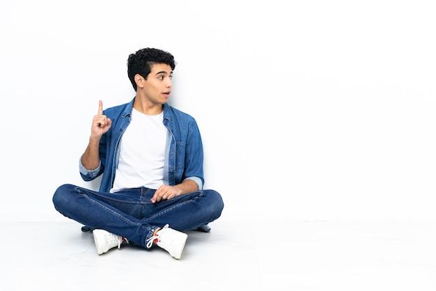 Venezolaanse man zittend op de vloer en denkt een idee met de vinger omhoog