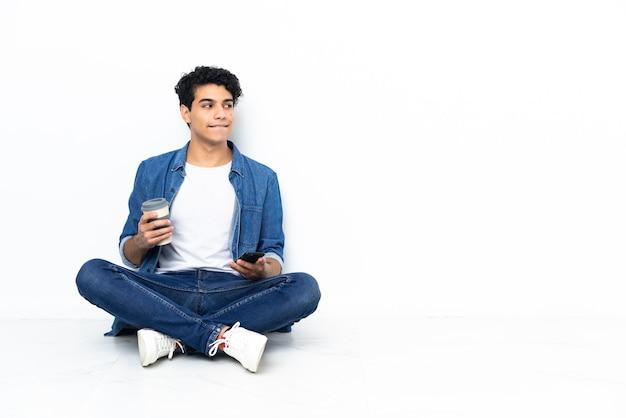 Venezolaanse man zittend op de vloer met koffie om mee te nemen en een mobiel terwijl hij iets denkt