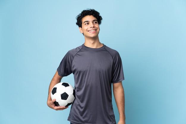 Venezolaanse voetballer man over geïsoleerde achtergrond een idee denken terwijl opzoeken