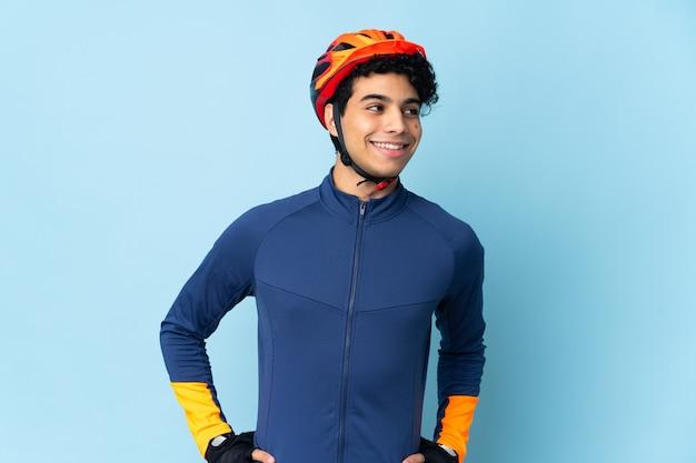 Venezolaanse wielrenner man geïsoleerd op blauwe achtergrond poseren met armen op heup en glimlachen