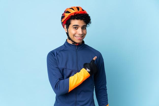 Venezolaanse wielrenner man op blauw wijst naar de zijkant om een product te presenteren