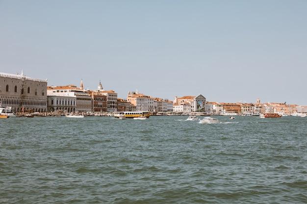Venice, italië - 1 juli 2018: panoramisch uitzicht op de kust van venetië met historische gebouwen en laguna veneta met botenverkeer. landschap van zonnige zomerdag en blauwe lucht