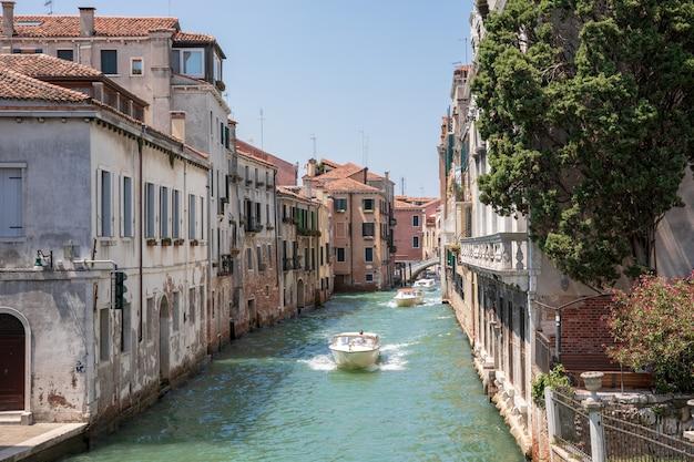 Venice, italië - 1 juli 2018: panoramisch uitzicht over het smalle kanaal van venetië met historische gebouwen en boten vanaf de brug foscari. landschap van zonnige zomerdag en blauwe lucht