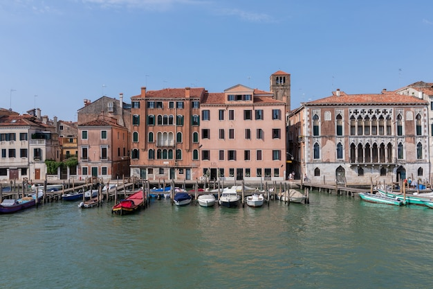 Venice, italië - 1 juli 2018: panoramisch uitzicht over het smalle kanaal van venetië met historische gebouwen en boten vanaf de brug. landschap van zonnige zomerdag