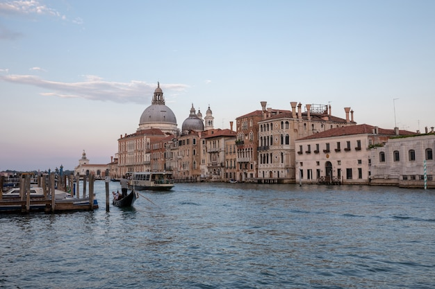 Venice, italië - 30 juni, 2018: panoramisch uitzicht over de canal grande van venetië met historische gebouwen, gondel en boten, weg van basilica salute. landschap van zomeravonddag en kleurrijke lucht