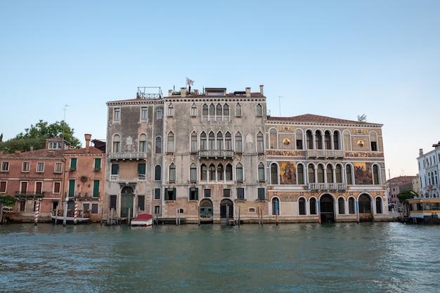 Venice, italië - 30 juni, 2018: panoramisch uitzicht over het canal grande van venetië met historische gebouwen en gondel. landschap van zomeravonddag en kleurrijke lucht