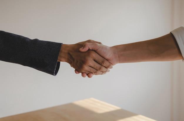 Vennootschap. twee mensen uit het bedrijfsleven de hand schudden na het ondertekenen van een contract