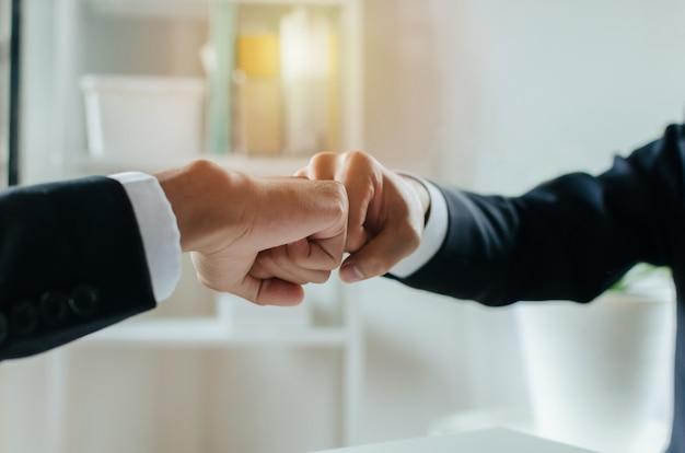 Vennootschap. twee zakenman investeerder hand aan vuist stoten en de handen ineen slaan na volledige zakelijke deal in vergaderzaal thuiskantoor, teamwork samenwerken, onderhandeling en financieel concept