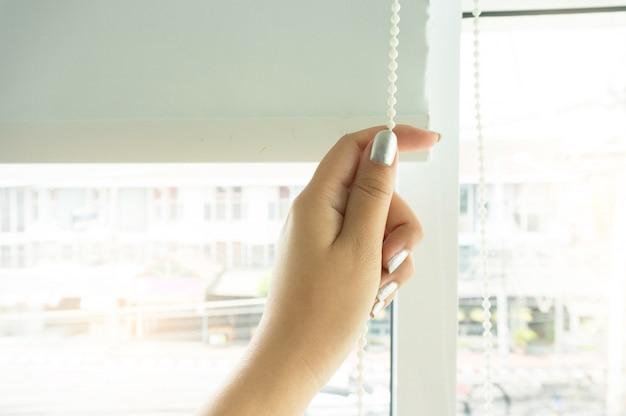 Venster gordijn sluiter door vrouw handen installeren venster jaloezieën, close-up.