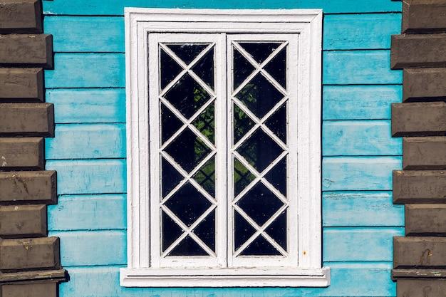 Venster in het oude houten blauwe huis in de zomer
