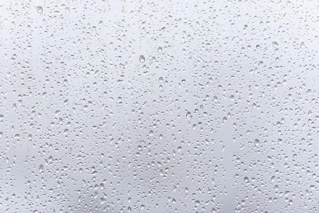 Venster met druppels na zware regen, waterdruppels op glas als achtergrond of textuur