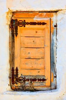 Venster met gesloten oud houten blind, mykonos-eiland, griekenland