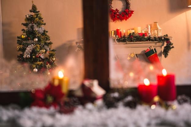 Venster met kaarsen en sneeuw en een kersttafereel achtergrond