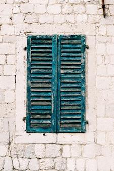 Venster met oude armoedige luiken op een witte bakstenen muur
