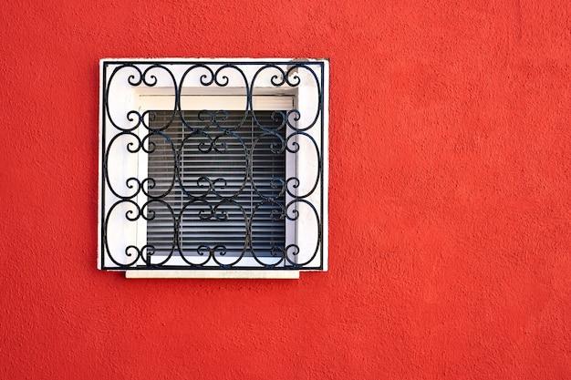 Venster met rooster op rode muur. italië, venetië.