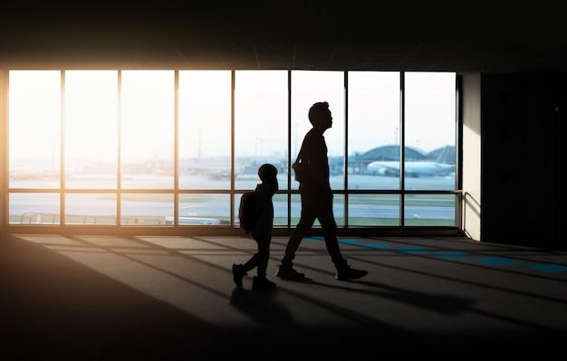 Venster met silhouetmensen op luchthaven.
