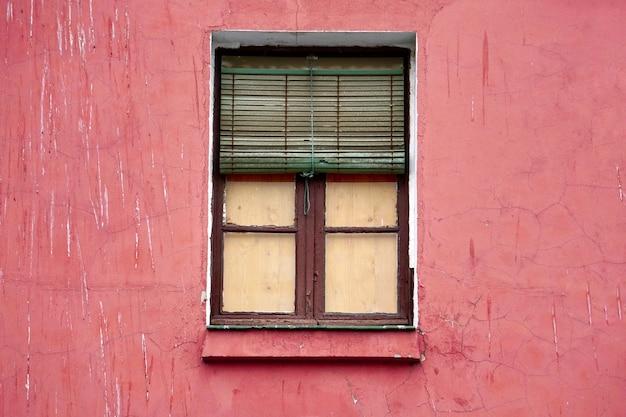 Venster op de rode gevel van het huis, de stadsarchitectuur van bilbao