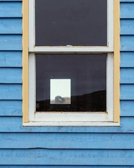 Venster op een houten blauwe muur van een huisje