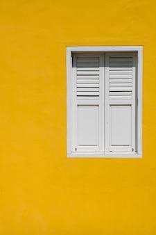 Venster op gele muur