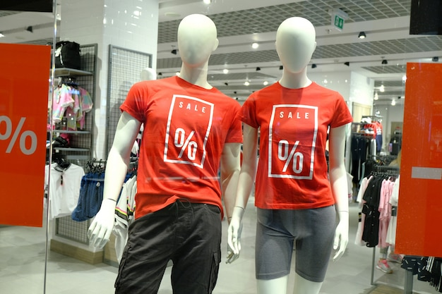 Venster van boutique met twee mannequins in t-shirts met borden reclame verkoop voor sportkleding.