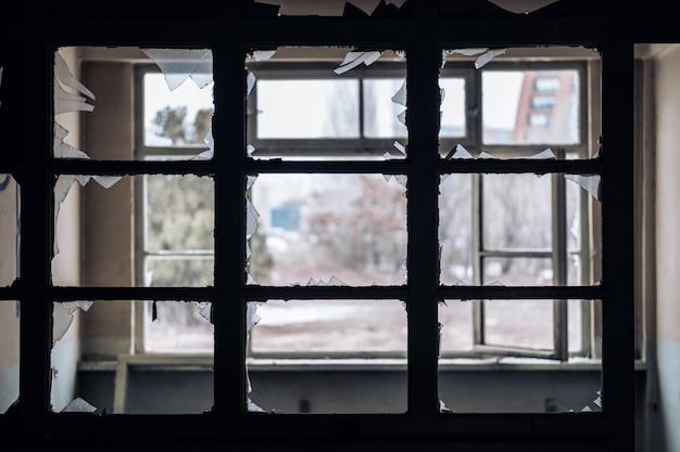 Venster van een leeg verlaten oud gebouw met gebroken glazen