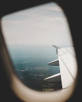 Venster van het vliegtuig met uitzicht op de groene velden erboven en de rechtervleugel