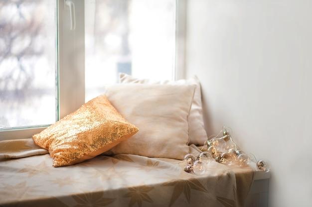 Vensterbank en kussens, lege ruimte. gouden kussen met pailletten, raam, slinger.