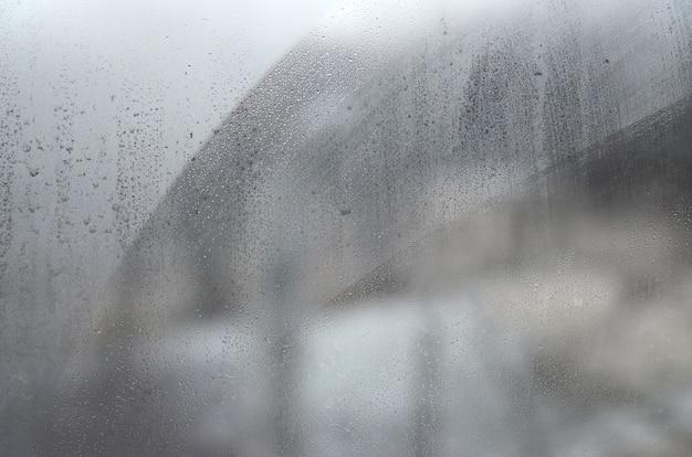 Vensterglas met condensaat of stoom na zware regen, textuur of achtergrond