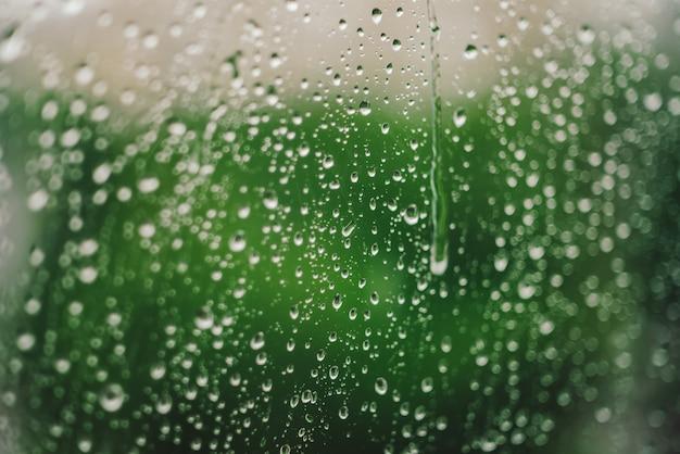 Vensterglas met druppels regen. atmosferische groene achtergrond met regendruppels in bokeh. druppeltjes sluiten omhoog. gedetailleerde transparante textuur in macro met kopie ruimte. regenachtig weer. isolatie concept.