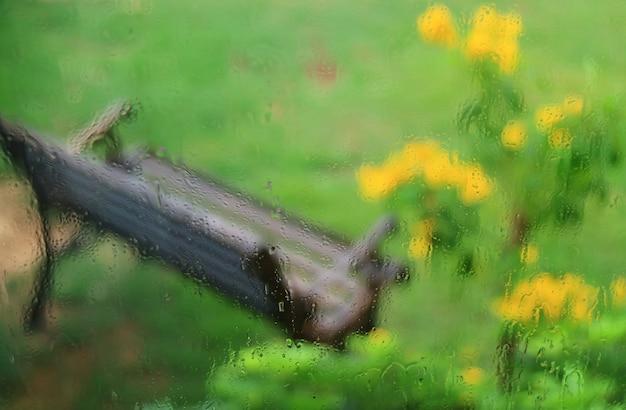Vensterglas met regendruppels en onscherpe tuinbank op achtergrond