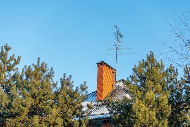 Ventilatie of schoorsteenpijp van oranje bakstenen op een besneeuwd dak van een landhuis met tv-antennes op blauwe hemel