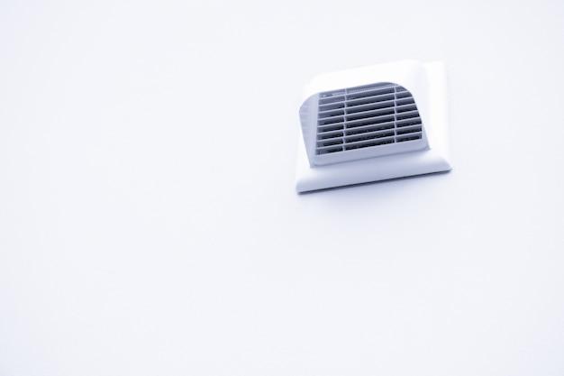 Ventilatierooster op de witte muur. kunststof witter ventilatierooster in badkamer, wandventilatierooster