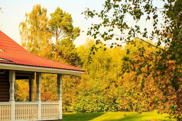Veranda met rood dak tegen de achtergrond van een herfstbos op een zonnige warme dag huisvesting in de natuur i...