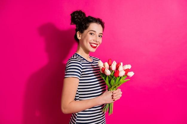 Veranderde mooie positieve vrolijke meid houdt natuurlijk boeket tulpen vast