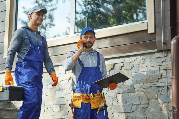 Verantwoordelijk arbeidersportret van twee drukke jonge reparateurs in blauwe overalls die gereedschapskist dragen