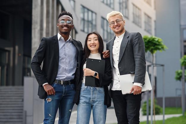 Verantwoordelijk internationaal zakelijk team van drie medewerkers analyseert papieren documenten van project in de buurt