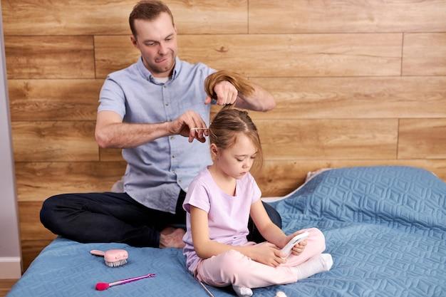 Verantwoordelijke vader vader kleine dochters haar vlechten, voorbereidingen voor school, knappe mannelijke zorgzame kind meisje zittend op bed