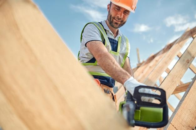 Verantwoordelijke werknemer die een helm en handschoenen draagt terwijl hij veilig een kettingzaag gebruikt
