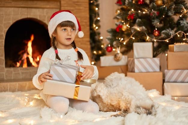 Verbaas meisje met geschenkdozen die op de vloer zitten en wegkijken