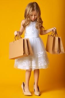 Verbaasd aantrekkelijk kind in kleding en grote schoenen die boodschappentassen op geel houden