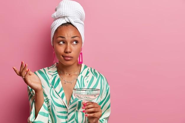 Verbaasd aarzelend donkere huid gezonde vrouw steekt hand op en kijkt twijfelachtig opzij, poseert met een cocktail