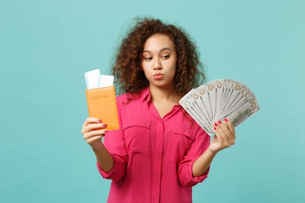 Verbaasd afrikaans meisje houdt paspoort instapkaart ticket fan van geld in dollarbankbiljetten contant geld geïsoleerd op blauwe turkooizen achtergrond. mensen oprechte emotie levensstijl concept. bespotten kopie ruimte.