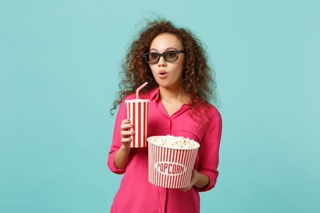 Verbaasd afrikaans meisje in 3d imax bril kijken naar film film houd popcorn, kopje frisdrank geïsoleerd op blauwe turkooizen achtergrond in studio. mensen emoties in de bioscoop, lifestyle concept. bespotten kopie ruimte.