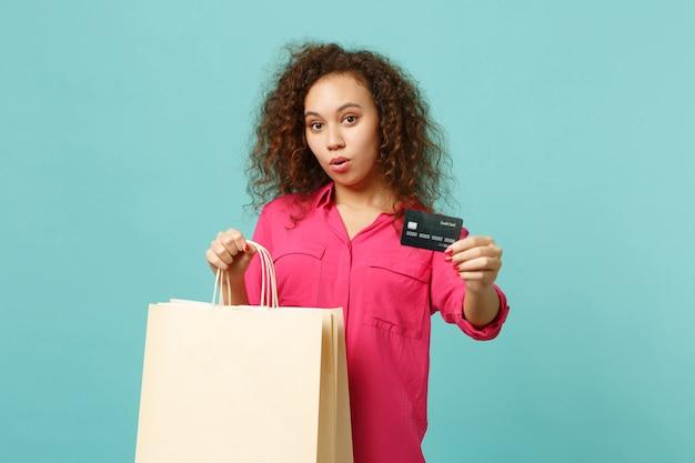 Verbaasd afrikaans meisje in vrijetijdskleding houdt pakkettas met aankopen vast na het winkelen met creditcard geïsoleerd op blauwe turkooizen achtergrond. mensen oprechte emoties levensstijl concept. bespotten kopie ruimte.