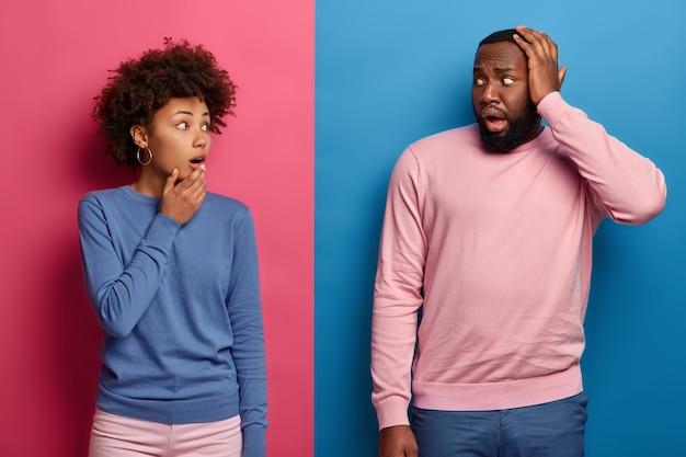 Verbaasd afro-paar staren elkaar verlegen aan, hebben moeite, denken samen na hoe het probleem kan worden opgelost, hebben afluisterogen, donkere huid