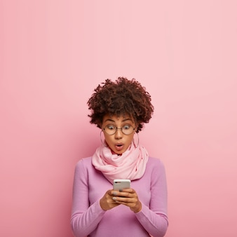 Verbaasd bang donkerhuidige duizendjarige vrouw controleert e-mail via smartphone, heeft geschokte uitdrukking, surft op internet